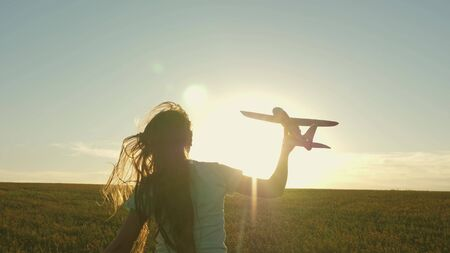 Happy girl runs with a toy airplane on a field in the sunset light. children play toy airplane. teenager dreams of flying and becoming pilot. the girl wants to become pilot and astronaut. Slow motion