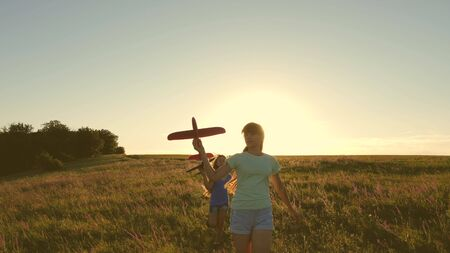 Dreams of flying. Happy childhood concept. Two girls play with a toy plane at sunset. Children on background of sun with an airplane in hand. Silhouette of children playing on the plane
