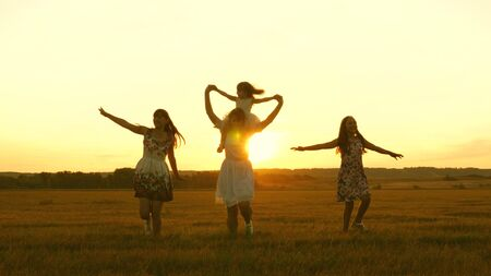 happy childhood concept. Happy young family with a child run across field in flight at sunset light. Mother and daughters walks in park and play in the meadow in sun. concept of life of a large family Stockfoto - 134208974