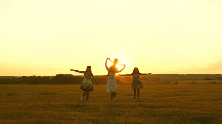 happy childhood concept. Happy young family with a child run across field in flight at sunset light. Mother and daughters walks in park and play in the meadow in sun. concept of life of a large family