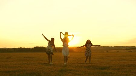 happy childhood concept. Happy young family with a child run across field in flight at sunset light. Mother and daughters walks in park and play in the meadow in sun. concept of life of a large family Stockfoto - 134208988