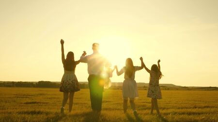 mother, father and little daughter with sisters walking in the field in the sun. Happy young family. Children, dad and mom play in the meadow in the sunshine. The concept of a happy family. Stockfoto