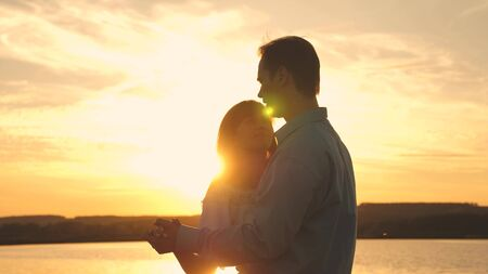 Young couple dancing at sunset on beach. Loving man and woman dance in bright rays of sun on the background of the lake. Happy guy and girl waltz in the evening in the summer park.