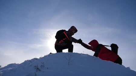 team work and victory. Tourists extends hand to friend that rises to top of hill. team of business people go to victory and success. team work of business people. climbers climb a snow-covered hill.