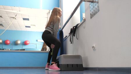 child crouches with dumbbell in hand. training in a fitness club. girl strengthens muscles of legs. Fitness club, teenager goes in for sports. Sport lifestyle concept. health promotion in gym.