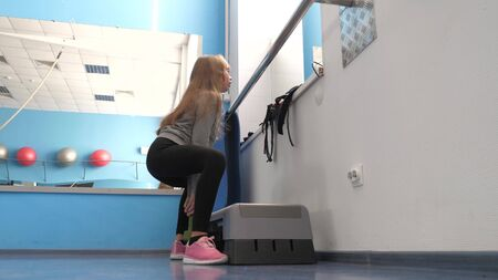 child crouches with dumbbell in hand. training in a fitness club. girl strengthens muscles of legs. Fitness club, teenager goes in for sports. Sport lifestyle concept. health promotion in gym. Zdjęcie Seryjne - 134740235