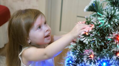 little girl examines a garland on Christmas tree. child plays by Christmas tree in childrens room. beautiful artificial christmas tree . happy childhood concept. Family plays for Christmas holidays
