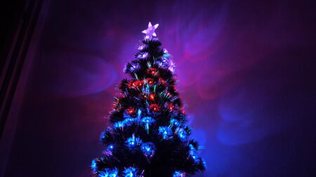 beautiful Christmas tree in room, decorated with a luminous garland and a star. holiday for children and adults. New Year 2020 mood. Christmas tree, happy holidays. Christmas interior. Stock Photo