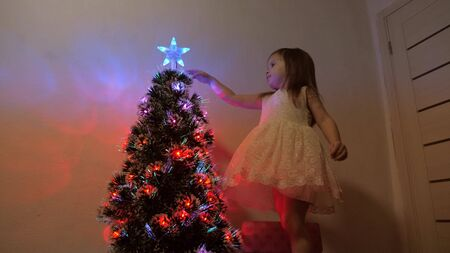 child examines a christmas star on a holiday tree. little girl plays near a Christmas tree in a childrens room. beautiful artificial christmas tree. The concept of a happy childhood.