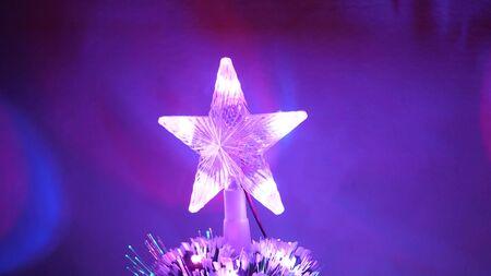 beautiful christmas star shining on christmas tree. New Year 2020 mood. Christmas tree, happy holidays. Christmas interior. holiday for children and adults.