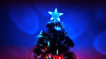 New Year 2020 mood. Christmas tree, happy holidays. Christmas interior. beautiful Christmas tree in room, decorated with a luminous garland and a star. holiday for children and adults. Stock Photo