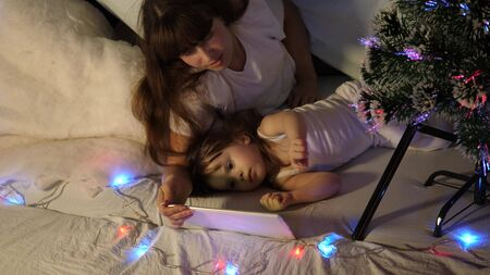 happy mother and daughter on Christmas evening, play cartoons and watch cartoons on tablet, in a childrens room in a tent with garlands. baby and mother are playing in room. happy childhood concept.