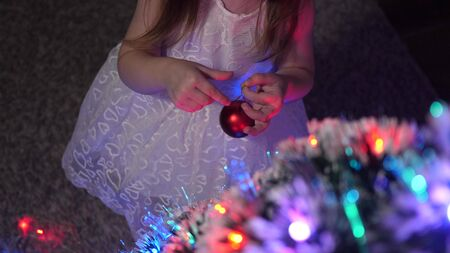child decorates the Christmas tree with Christmas balls. small kid plays by Christmas tree in childrens room. daughter examines garland on Christmas tree. happy childhood concept. Stock fotó