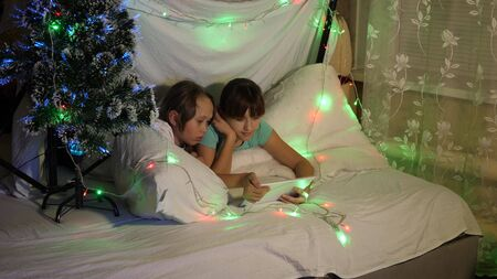 concept of a family Christmas. children on Christmas evening play on tablet, in childrens room on couch garlands. sisters play in a room decorated with a multi-colored New Year tree Stock fotó