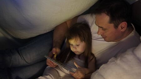 concept of a family Christmas. child and dad on Christmas evening play on tablet, in childrens room, in tent with garlands. baby and father are playing in room. concept of happy childhood and family.