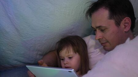 Father and daughter on Christmas evening, play and watch cartoons on tablet, in a childrens room in a tent with garlands. baby and dad are playing in room. concept of happy childhood and family. Stock fotó