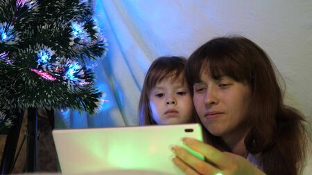 mom and daughter on Christmas evening, play and watch cartoons on tablet, in a childrens room in a tent with garlands. baby and mother are playing in the room. concept of happy childhood and family.