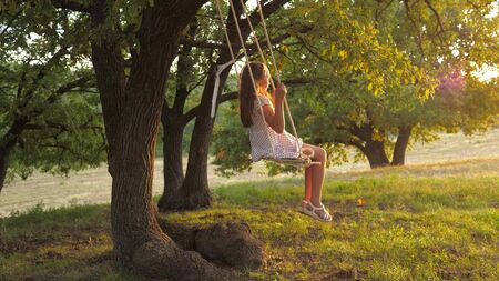 child swinging on a swing in park in sun. young girl swinging on rope swing on an oak branch. teen girl enjoys flight on swing on summer evening in forest. concept of happy family and childhood.