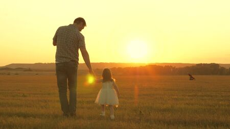 little daughter walks with her father in a meadow holding hands. child holds fathers hand. family walks in evening out of town. dad and baby are resting in the park. child plays with his father