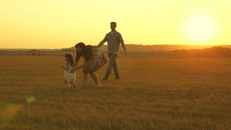 Happy child and parents walk at sunset. Dad hugs daughter and whirls in flight. Silhouette of a family walking in the sun. Mom dad and baby. The concept of a happy family. Family lifestyle Stock fotó