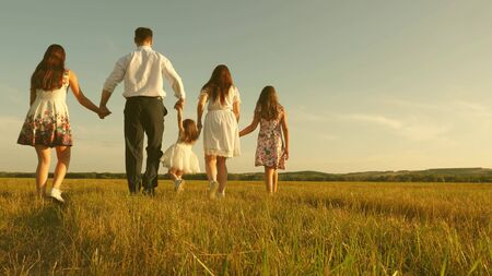 concept of a happy childhood. mother, father and little daughter with sisters walking in field in the sun. Happy young family. Children, dad and mom play in meadow in sunshine. concept of happy family