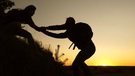 female traveler holds the hand of a male traveler helping to climb top of the hill. Tourists climb the mountain at sunset, holding hands. team work of business partners. Happy family on vacation.