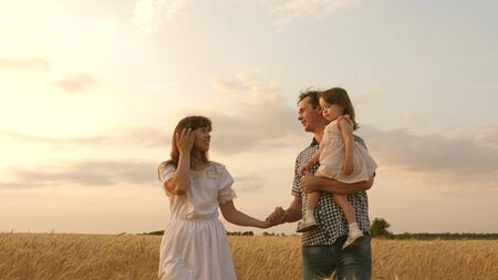 baby in the arms of father and mother. Happy family holding hands on walks. little daughter, dad and mom play in a wheat field. baby travels across field with her family. child and parent are playing. Stock fotó