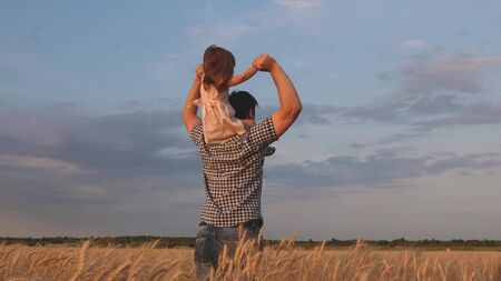 little happy daughter on fathers shoulders in field against the blue sky. baby boy and dad travel on a wheat field. child and parent play in nature. happy family and childhood concept. Slow motion