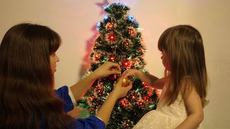 child and mother decorate tree with christmas balls. baby and mom hang a red ball toy on Christmas tree. happy childhood concept. small child and a parent are playing by Christmas tree.