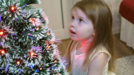 Happy little baby is playing near the Christmas tree and smiling. The girl strokes her hairy beautiful spruce. Smart spruce. New Year. Christmas Holidays