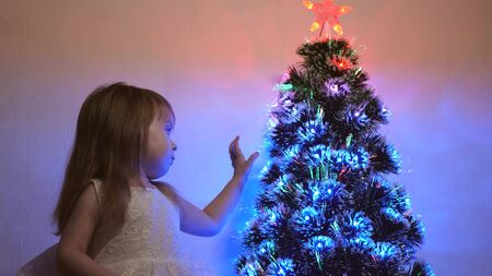 small child plays by Christmas tree in childrens room. daughter examines garland on Christmas tree. beautiful artificial christmas tree . happy childhood concept. Family plays for Christmas holidays Stock fotó