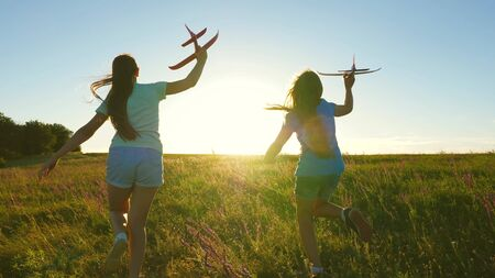 Happy childhood concept. Dreams of flying. Two girls play with toy plane at sunset. Children on background of sun with an airplane in hand. Silhouette of children playing on plane