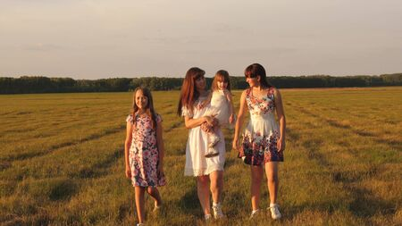 Children and mom are playing in the meadow. concept of a happy family. mother and little daughter with sisters walking in park. Happy young family with a child walking on a summer field. Stock fotó