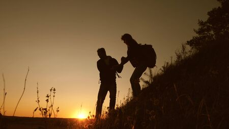 Travelers descend from mountain at sunset, hold hands. adventure and travel concept. teamwork of business people. Hiker man holds out his hand to woman traveler descending from top of hill.