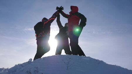 travelers met on top of success. Tourists come to top of snowy hill and rejoice at victory against backdrop of yellow sunset. teamwork and victory. team work of people in difficult conditions Stock fotó
