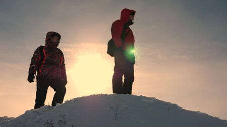 Travelers on a snowy mountain are guided by terrain and choose direction of movement. Alaskan travelers go to the top of a snowy hill. team work of people. business teamwork, victory and success.