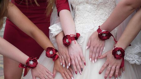 beautiful hands of the bride and bridesmaids. wedding party. girls hands are decorated with red flowers. fashion girls