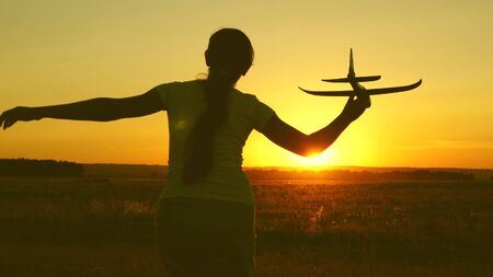 children play toy airplane. Happy girl runs with a toy airplane on a field in the sunset light. teenager dreams of flying and becoming pilot. the girl wants to become a pilot and astronaut.