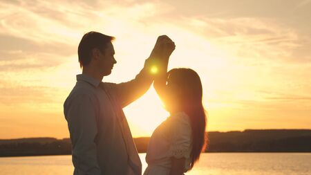 Loving man and woman dance in bright rays of sun on the background of the lake. Young couple dancing at sunset on beach. Happy guy and girl waltz in the evening in the summer park.