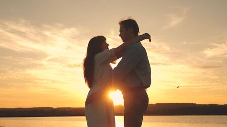 Loving man and woman dance in bright rays of sun on the background of the lake. couple dancing at sunset on beach. Happy guy and girl waltz in the evening in the summer park. Standard-Bild - 140192591