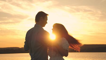 Loving man and woman dance in bright rays of sun on the background of the lake. Young couple dancing at sunset on beach. Happy guy and girl waltz in the evening in summer park. Standard-Bild - 140193494