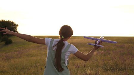 young girl runs with a toy plane on the field in the rays of slint. children play toy airplane. teenager dreams of flying and becoming a pilot. the girl wants to become a pilot and astronaut. Stockfoto