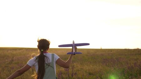 young girl runs with a toy plane on field in the rays of slint. children play toy airplane. teenager dreams of flying and becoming a pilot. the girl wants to become a pilot and astronaut.