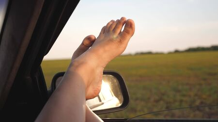 bare feet of a girl in a car window, glare of the sun, riding a car on a country road. woman travels by car. young woman likes to travel in car, putting her legs out of an open window.