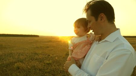 father teaches little daughter in the park. concept of happy family and childhood. Dad and mom playing with a little daughter in her arms at sunset. family walks with the child at sunset.