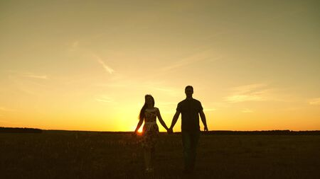 beautiful girl and guy go hand in hand in rays of sun in spring. happy family walking in park in summer, happy family concept. A young couple in love walks and listens to music on a smartphone. 免版税图像