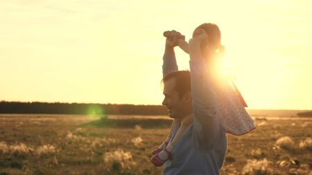 Dad with his beloved daughter on his shoulders dances in flight and laughs. Happy child plays with his father on a sunset field. Silhouette of a man and a child. Family and Childhood Concept