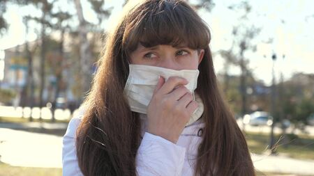 Young sick woman in medical protective mask coughs on street. the girl is infected coughing. Carrier, Covid-19, coronavirus, symptom. Pandemic Coronavirus. a person with the flu. close-up