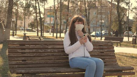 Coronavirus protection. young woman in a medical protective mask is sitting with a smartphone on city street in Europe. tourists on street wear protective mask from viruses. concept health and safety