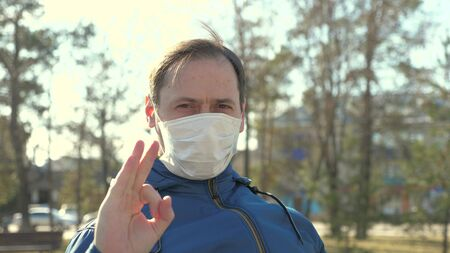 Flu pandemic. a man puts on a medical protective mask on street in a city. show ok. close-up. health and safety concept, coronavirus N1H1, virus protection. health and safety concept. Stock Photo